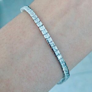 modern tennis bracelet with desert diamond simulants of size 2.5 millimeter square princess cut with a semibezel setting pictured on a woman's wrist
