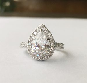 stunning antique style tear drop halo engagement ring showing large diamond surrounded by 12 smaller diamonds on a half band of 5 more smaller diamond simulants on either side